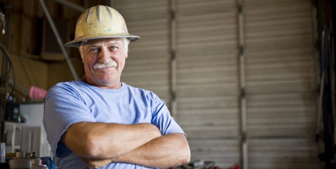 Senior man in warehouse wearing hard hat